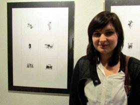 Karolina Gilewicz na tle plansz wystawowych ze swoimi pracami